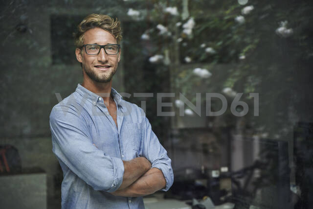 Portrait of casual young businessman behind windowpane in office - PNEF02085 - Philipp Nemenz/Westend61