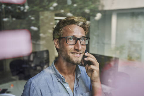 Casual young businessman on the phone behind windowpane in office - PNEF02091