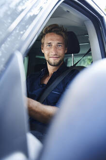 Portrait of confident young man in car - PNEF02103