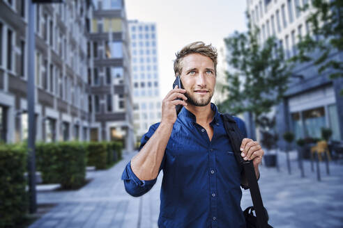 Confident young businessman on the phone in the city - PNEF02109