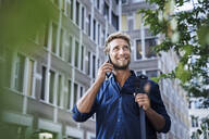 Smiling young businessman on the phone in the city - PNEF02112