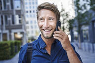 Portrait of happy young businessman on the phone in the city - PNEF02115