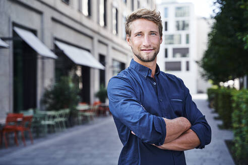 Portrait of confident young businessman in the city - PNEF02133