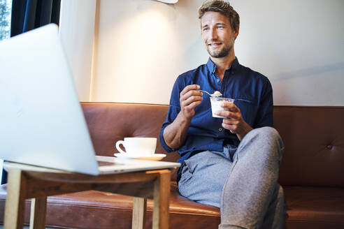 Young businessman eating and using laptop in a cafe - PNEF02139