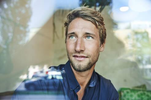 Portrait of young man behind windowpane - PNEF02145