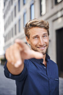 Portrait of confident young man in the city pointing his finger - PNEF02160