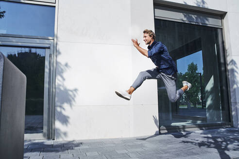 Young businessman jumping mid-air in the city - PNEF02166
