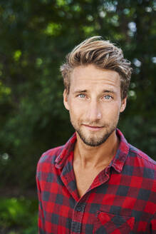 Portrait of confident young man wearing checkered shirt outdoors - PNEF02169