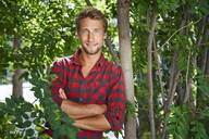 Portrait of confident young man wearing checkered shirt leaning against a tree - PNEF02172