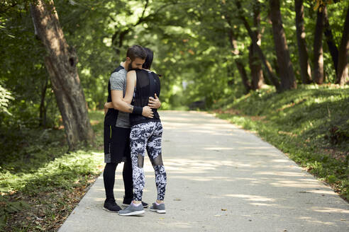 Sporty couple hugging on forest path - ZEDF02625