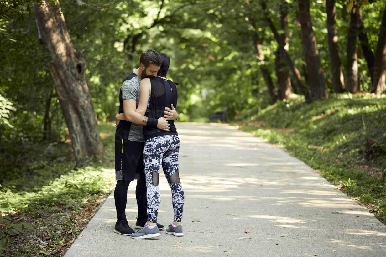 Sporty couple hugging on forest path - ZEDF02625 - Zeljko Dangubic/Westend61