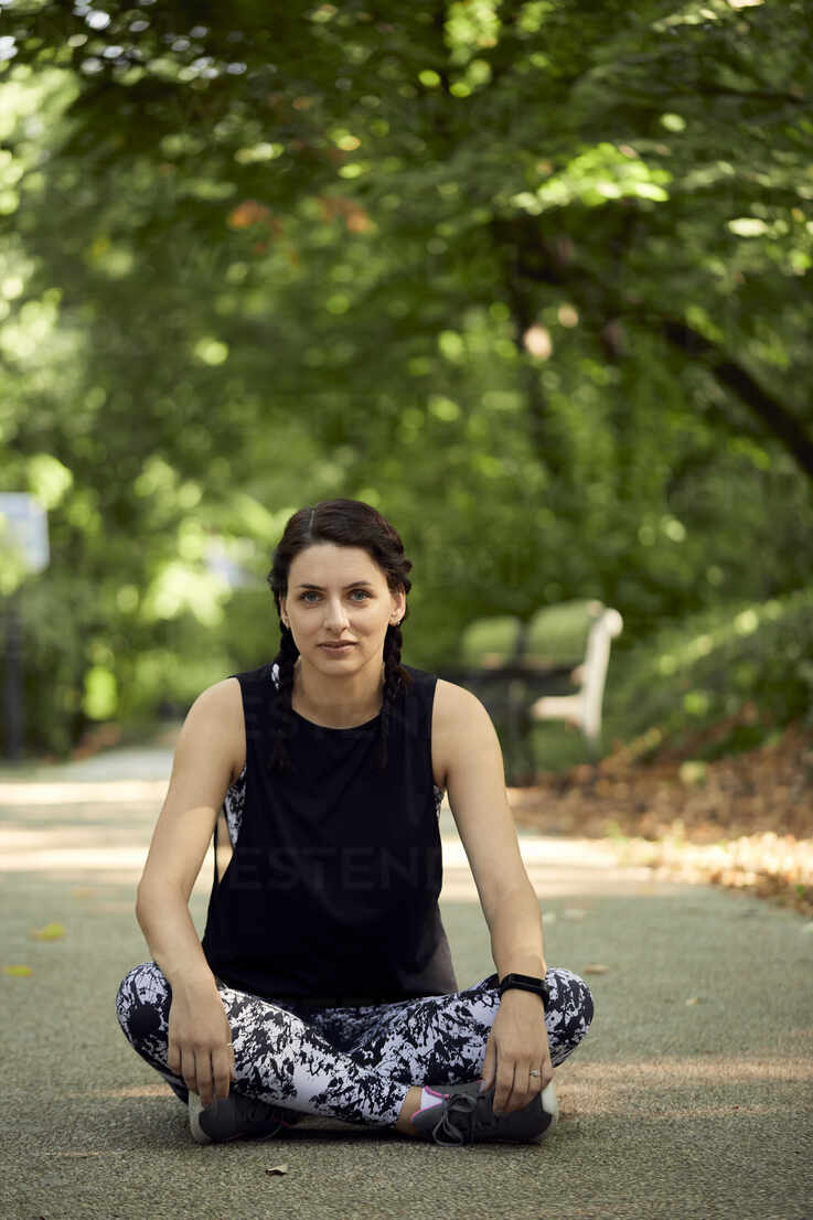 Portrait of sporty young woman sitting on forest path - ZEDF02637 - Zeljko Dangubic/Westend61