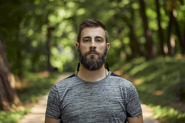 Portrait of sporty man with earphones in forest - ZEDF02640