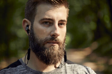 Portrait of sporty man with earphones in forest - ZEDF02643