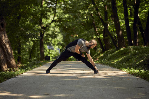 Sporty man stretching on forest path - ZEDF02646