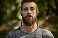 Portrait of sporty man with earphones in forest - ZEDF02649