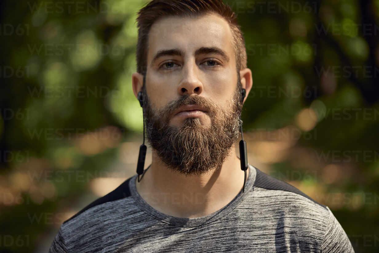 Portrait of sporty man with earphones in forest - ZEDF02649 - Zeljko Dangubic/Westend61