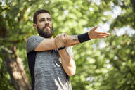 Sporty man stretching in nature - ZEDF02652