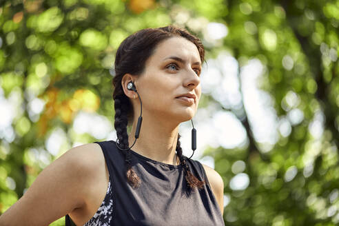 Portrait of sporty young woman with earphones in forest - ZEDF02655