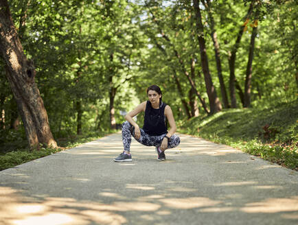 Portrait of sporty young woman crouching on forest path - ZEDF02658