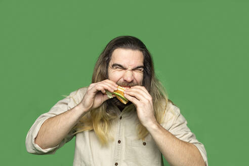 Portrait of bearded man eating sandwich in front of green background - VGF00309