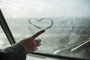 Woman's finger drawing a heart on the window of a van - NAF00129