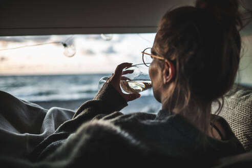 Young woman with glass of white wine in van - NAF00138