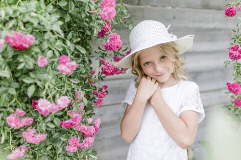 Portrait of smiling girl at rosebush - STBF00425