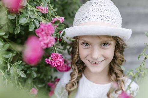 Portrait of smiling girl at rosebush - STBF00428