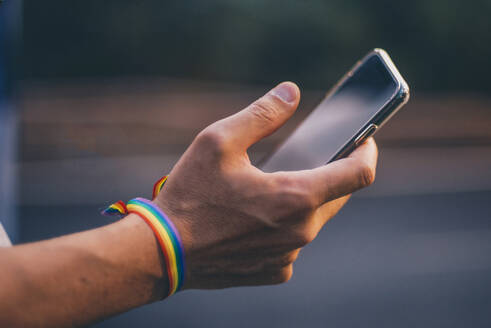 Hands of man with pusera gay flag holding an smartphone - CJMF00070