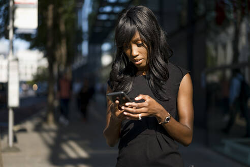 Businesswoman using smartphone in the city - MAUF02914