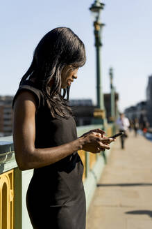 Businesswoman using smartphone on a bridge - MAUF02935