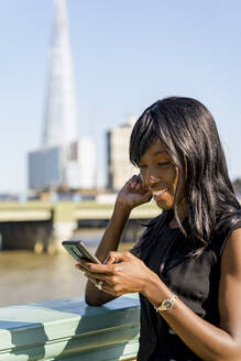 Businesswoman using smartphone in the city - MAUF02938