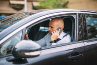 Businessman driving vehicle and using smartphone - CJMF00078
