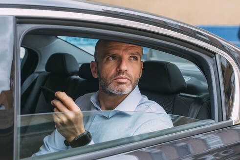 Businessman sitting on a backseat of a car using smartphone and looking around - CJMF00084