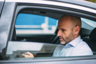 Businessman sitting on a backseat of the car using smartphone - CJMF00087