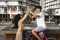 Young couple with bicycle, high-fiving in the city - RCPF00018