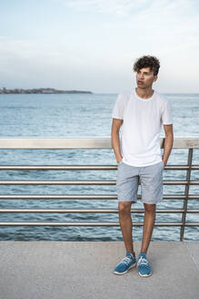 Young man standing on bridge by the sea, with hands in pockets - RCPF00027