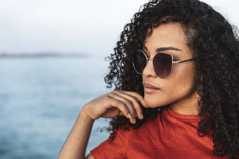 Beautiful woman, wearing sunglasses, standing at the sea, looking away - RCPF00042