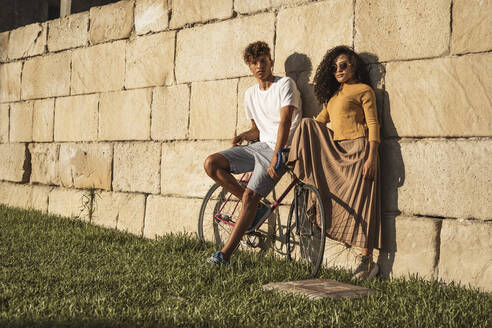 Young couple with bicycle, leaning on stone wall, looking cool - RCPF00051