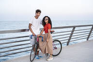 Young couple with bicycle, standing on bridge by the sea - RCPF00054