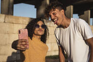 Young couple taking selfies with smartphone, sitting in front of wall - RCPF00060