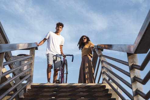 Young couple with bicycle, standing on top of stairs - RCPF00063