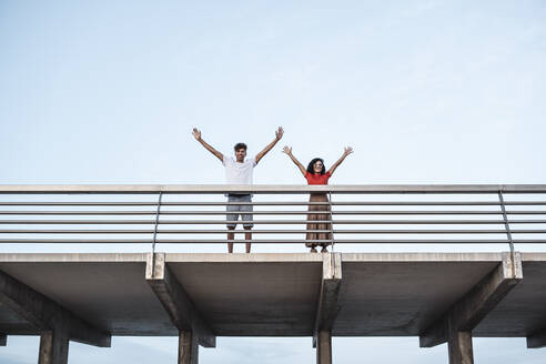 Young couple standing on bridge, waving with raised arms - RCPF00072