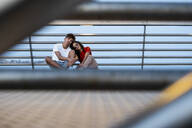 Young couple sitting on bridge by the sea - RCPF00078