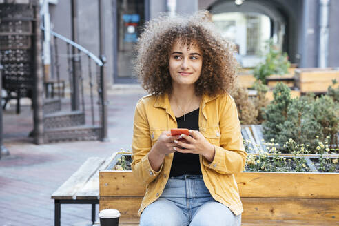 Portrait of smiling teenage girl sitting on bench with coffee and mobile phone - VPIF01534