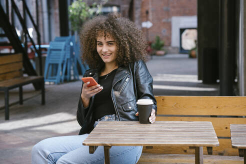 Portrait of smiling teenage girl sitting on bench with coffee to go and cell phone - VPIF01540