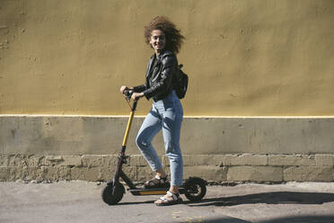 Smiling teenage girl with scooter in the city - VPIF01555