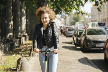 Portrait of happy teenage girl riding scooter in the city - VPIF01561