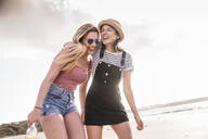 Two girlfriends having fun, walking on the beach - UUF19020